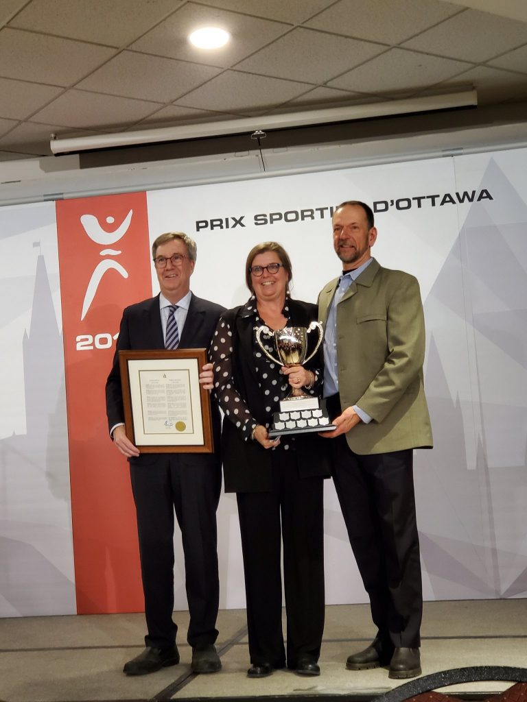 Mayor Jim Watson presents LA and Bevin Schmidt with the Mayor's Cup for their long-time dedication to amateur sports in Ottawa. Courtesy Maha El-Chantiry