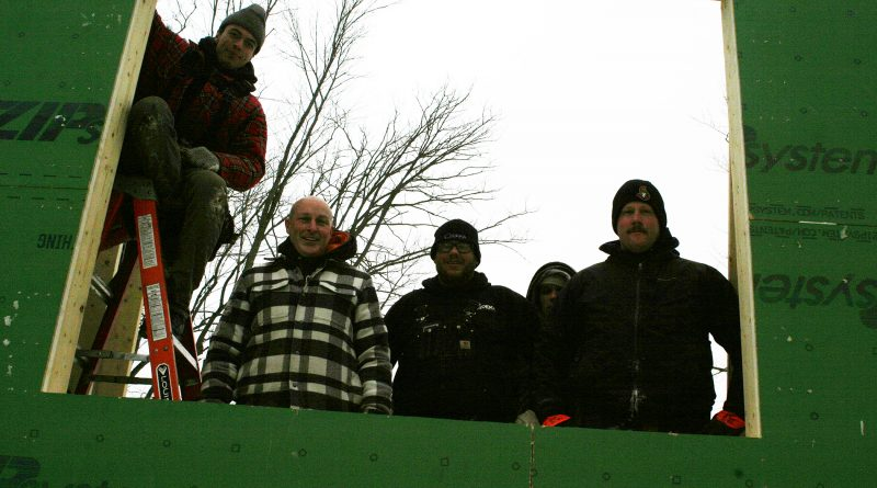 Ryan Littler, second from left, Deka's Dylan Sliter, right of Littler, and construction company owner Tom Taetz, foar right, as well as crew and family pose in the window frame of Littler's new home. Photo by Jake Davies