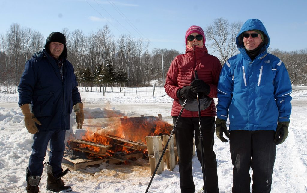 From left, volunteers George Wilson, Béatrice Romeskie and Dan Kovacs keep the fire burning along the cross-country ski trail. Photo by Jake Davies