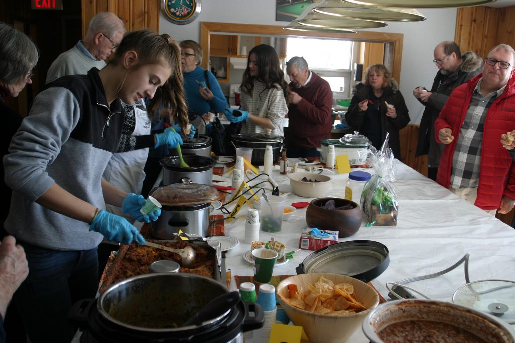 Volunteer Shanna Deugo, far left, helps serve hungry judges a sample of chili. Photo by Jake Davies