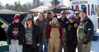 Mike Fine, far right, Peter Strong, third from left, and a gaggle of volunteers pose for a photo at Mike and Peter's 13th Annual Fishing Derby yesterday. Photo by Jake Davies