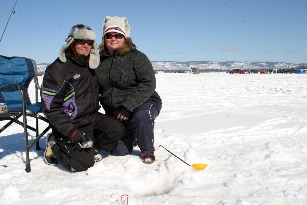From left, Fitzroy Harbour's Jody Brenton and Arnprior's Catherine Buffam-Jensen pose by their fishing holes. Photo by Jake Davies