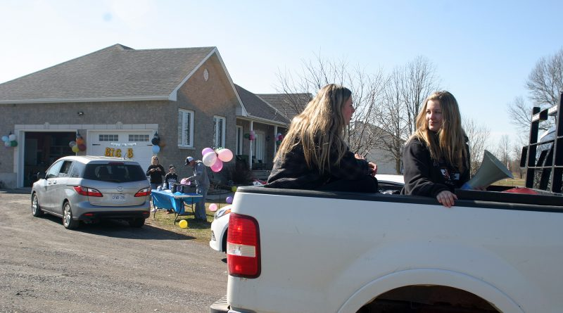 Cousins Avery and Carmen Beck ay happy birthday from the back of a truck during Braydan Delahunt's birthday parade Monday. Photo by Jake Davies