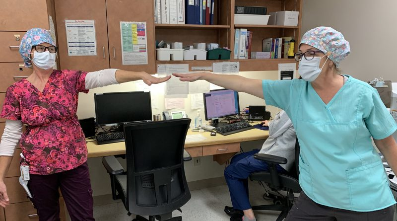 QCH nurses Tracey Zoobkoff, left, and Joyce Corley-Byrne practice physical distancing at the hospital. Zoobkoff is asking community sewers to help make scrub hats for needy nurses. Courtesy Zoobkoff