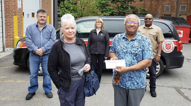 Janet McKeen-Peterkin and Bruce Peterkin, up front, present a cheque to Booth Centre managers Wednesday night. Courtesy Janet McKeen-Peterkin