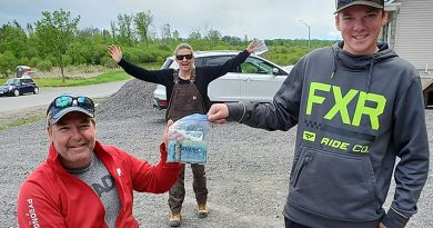 William Riley, right, makes the donation to Todd Nicholson that puts him over the $10,000 raised mark for the Abilities Centre Ottawa on Sunday, May 31. Emily Glossop Nicholson celebrates in the background. Courtesy Karen Riley