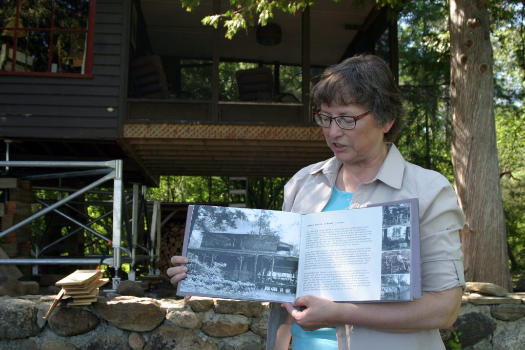 Shannon Gartner shows a historic photo of the Stapleton's summer home before it burned down in 1947. Photo by Jake Davies