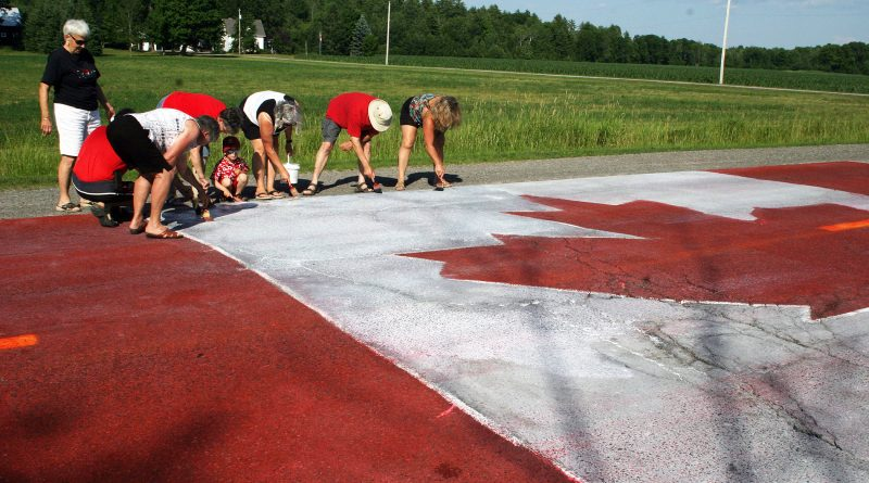 The Get'er Done Crew put the finishing touches on the Carp Road Canada Day flag, a tradition of roughly 28 years. Photo by Jake Davies