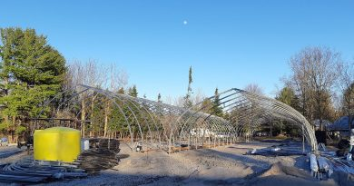 The Spinks family builds two greenhouses totalling 12,000 square feet on their Dunrobin property last April. Photo by Earl Spinks
