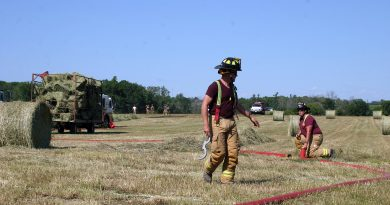 Volunteer firefighter Mike Brennan helps with clean-up after an afternoon hay fire near Kinburn. Photo by Jake Davies
