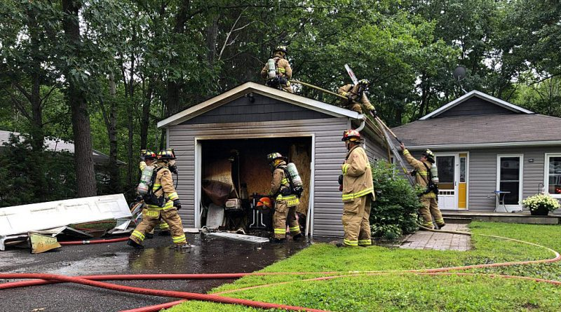 Volunteer firefighters tackle a garage fire this afternoon on Bayview Drive. Courtesy District 6 Chief Bill Bell