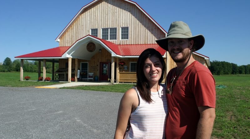 Greg Bell and Brianna Di Labio pose outside their new barn, the centrepiece of March Meadow Farm just outside of Dunrobin. Photo by Jake Davies