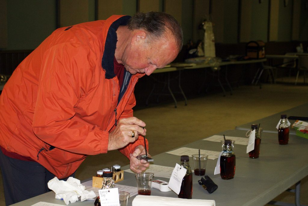 Michael Walters checks the suguar content of syrup submitted in the Carp Fair 2020 Showcase.