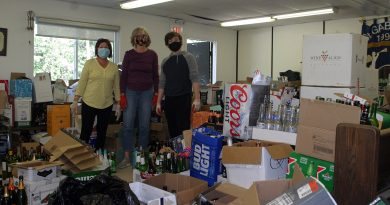 Volunteers pose with empty bottles.