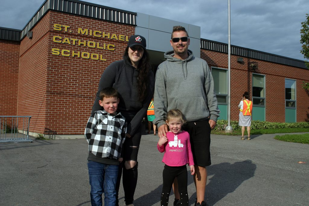 The Daze family poses for a photo in front of St. Michael's Catholic School.