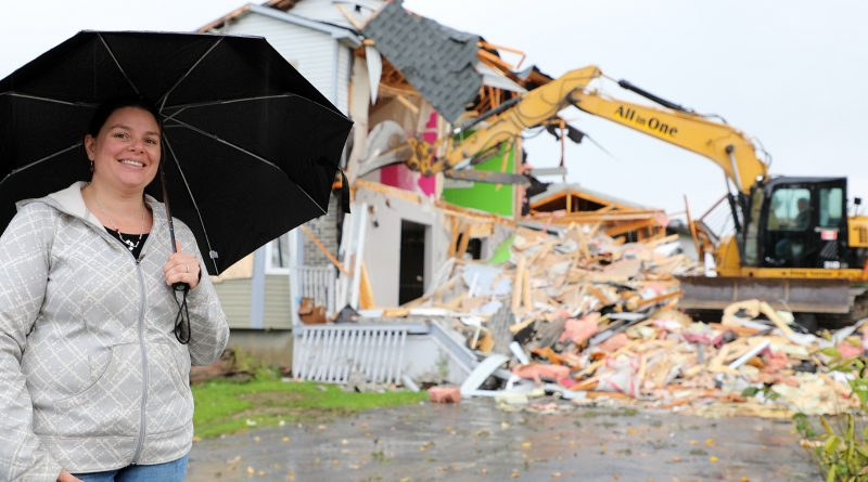 Grace Campbell poses for a photo while her home is destroyed in the background.