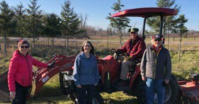 Carp Riverwalk volunteers pose in front of a tractor.