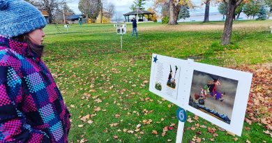 A young girl reads a story while on a story walk.