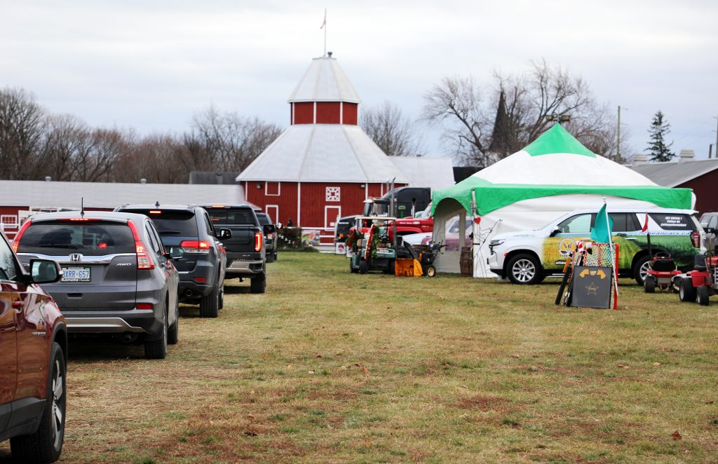 A line up of cars proceeds through Dave Creighton's drive-through wake Saturday.