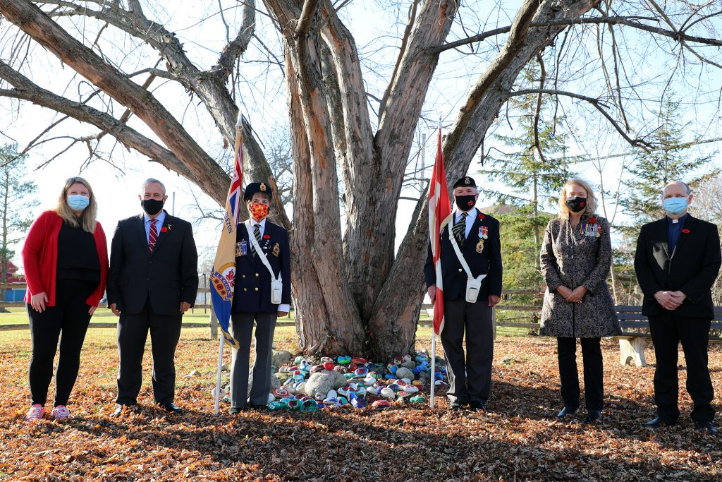 From left, St. Michael's Principal Chantel Couture-Campbell, Coun. Eli El-Chantiry, Colour Guard Arleen Morrow and Rob Gallant, MP Karen McCrimmon and Father John Orban pose in front of a large collection of symbolic Remembrance Day rocks.