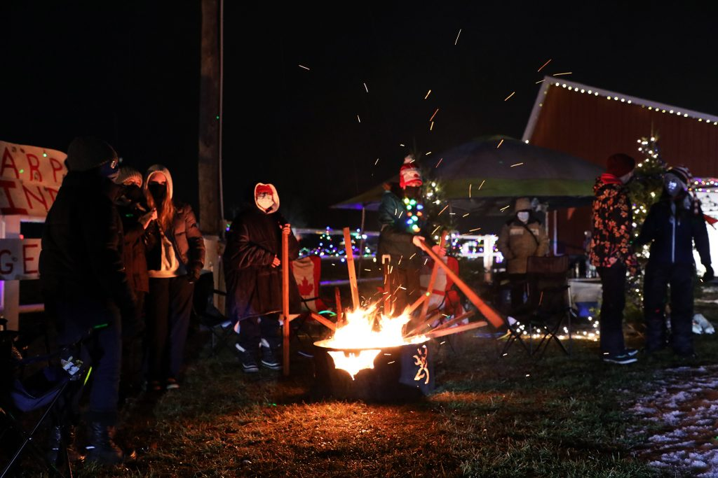 The 9th Carp Pathfinder Rangers keep warm by the fire during a parade that saw nearly 1,000 cars.