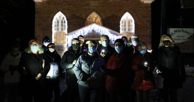 A group of carolers poses in front of St. Michael's Church last Saturday.