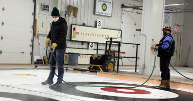 Huntley volunteers work on making curling ice.