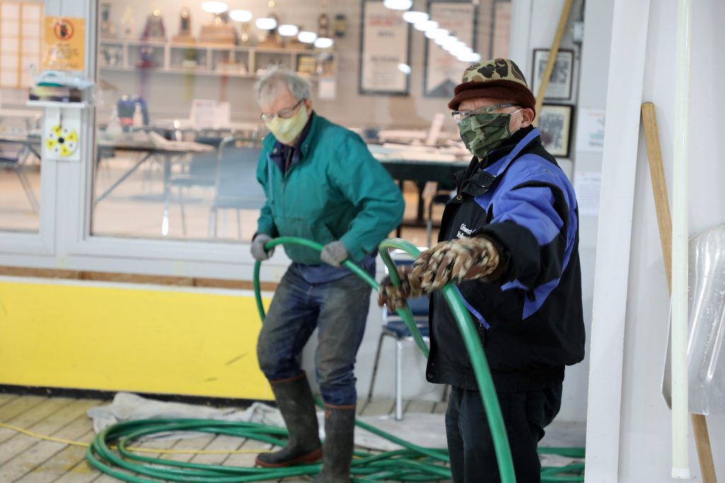 Two volunteers help make ice  at the curling club.
