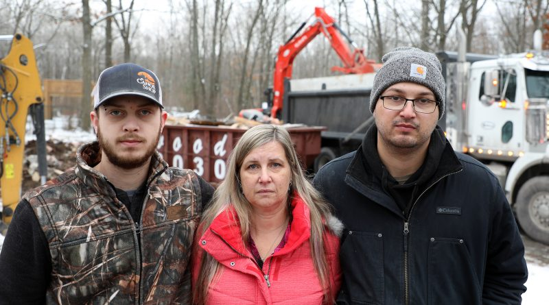 Sons Nick and Jonathon surround their mom Melissa Lepage as the family home is destroyed in the background.