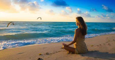 A woman meditates on the beach.
