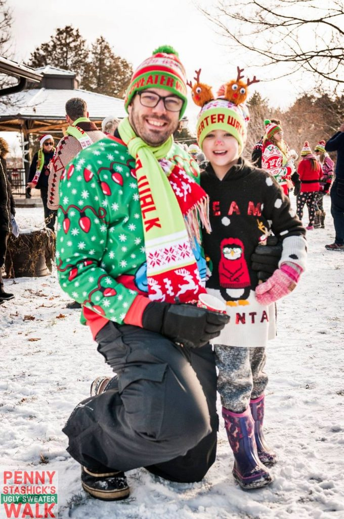 Event organizer Derek Stashik poses with his daughte at last year's Ugly Sweater Walk.
