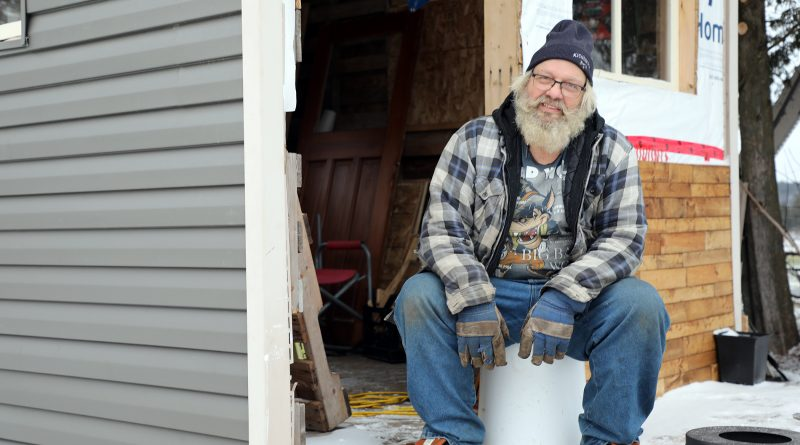 Guy Lamarche sits outside the bunkie he's building near Carp.