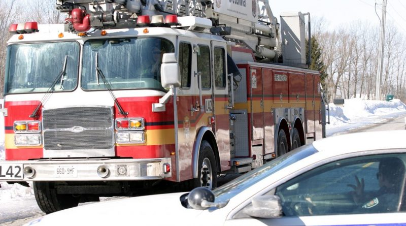 A West Carleton fire truck passes an Ottawa police car.