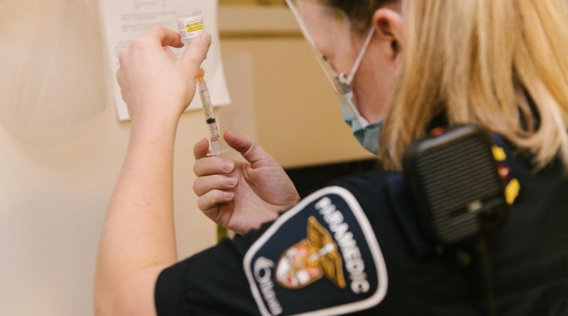 An Ottawa paramedic handles the COVID-19 vaccine.