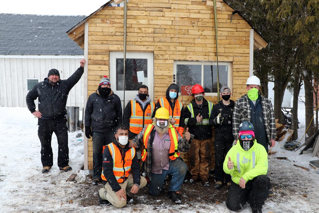 A group photo of the volunteers who moved the bunkie.