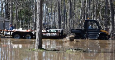 A photo of an ATV travelling a flooded area.
