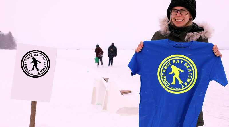 A photo of Jennie Joly holding a t-shirt with the Constance Bay Skateway logo on it.