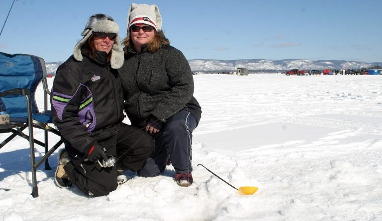 Fitzroy Harbour's Jody Brenton and Arnprior's Catherine Buffam-Jensen pose by their fishing holes during last year's fishing derby. Photo by Jake Davies