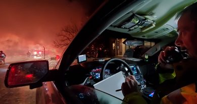 A firefighter works with dispatch from his car during last night's fire.