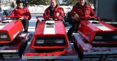 Three men on old sleds.