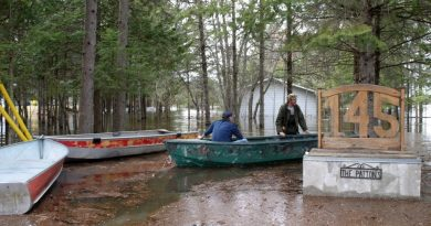 Vydon Acres resident navigate around their property in boats.