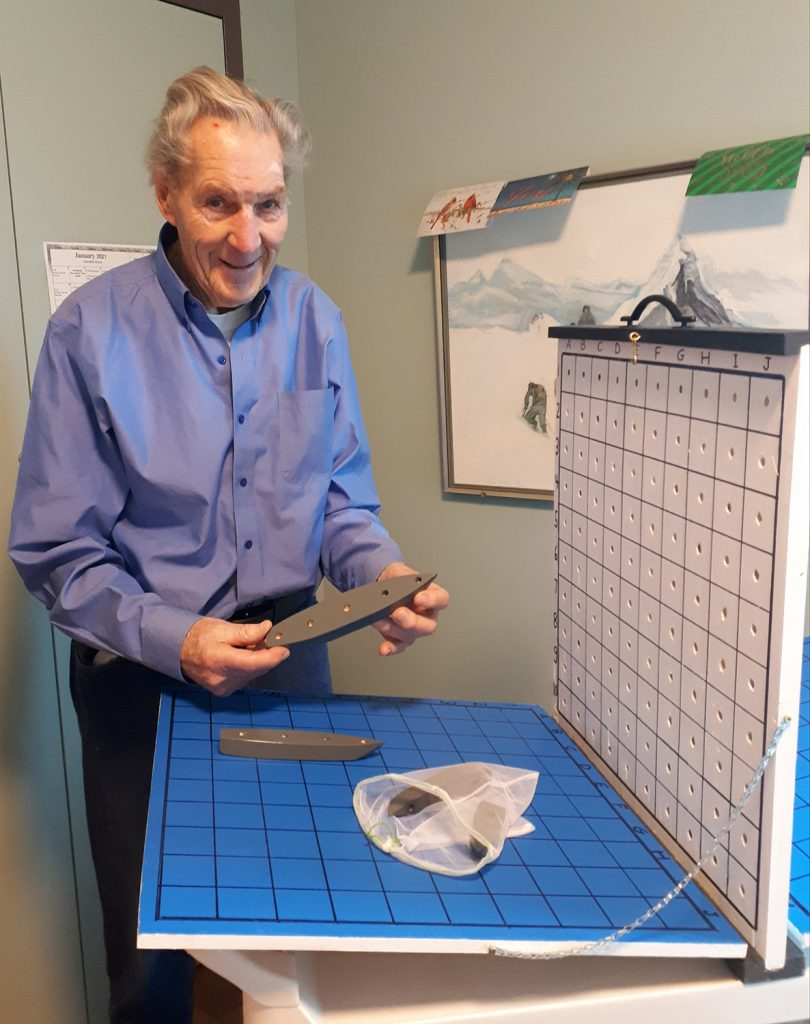 Fairview Manor resident Graham Burgess checks out the Battleship game, handmade by former neighbour Peter Baran. Courtesy Fairview Manor