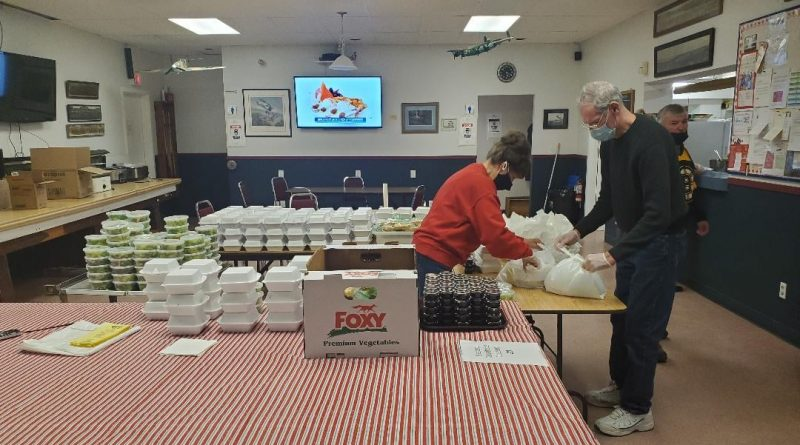The Legion's Arleen Morrow and President George Dolan pack dinners during the March 27 Meals to Wheels event.