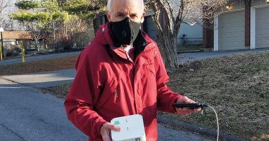 Breathe Easy Project lead Jake Cole shows off the air quality monitor used for the project's testing.