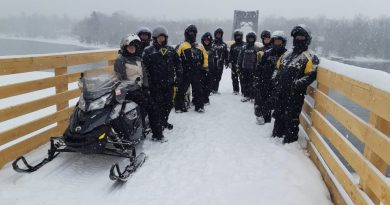 Snowmobilers pose on the world's longest snowmobile bridge.