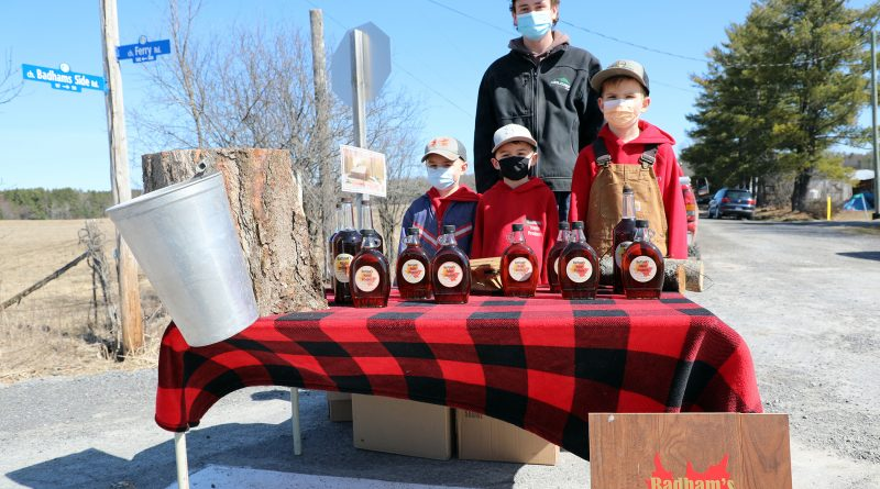 In front, from left, sixth-generation syrup makers Danny Badham, 6, Emmerson Graham, 6, and Lyal Badham, 7, with fifth-generation maker Austin Badham in back, pose at their Ferry Road stand last Saturday. Photo by Jake Davies