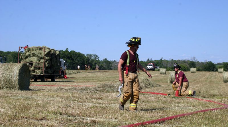A firefighter stands in a hay field.