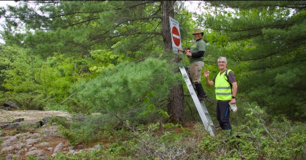 Volunteers install a sign along the trail.