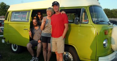 A family pose in front of their VW van.