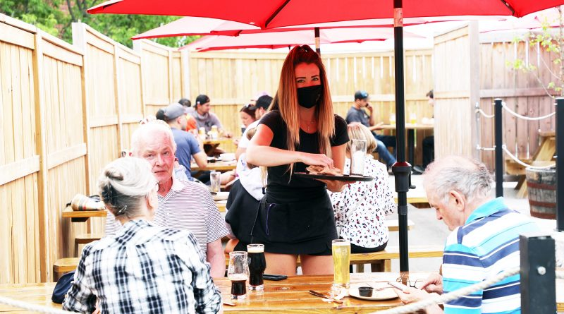 A photo of a server serving some guests.